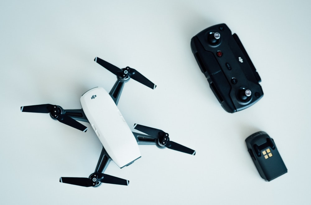 white and black quadcopter drone on white table