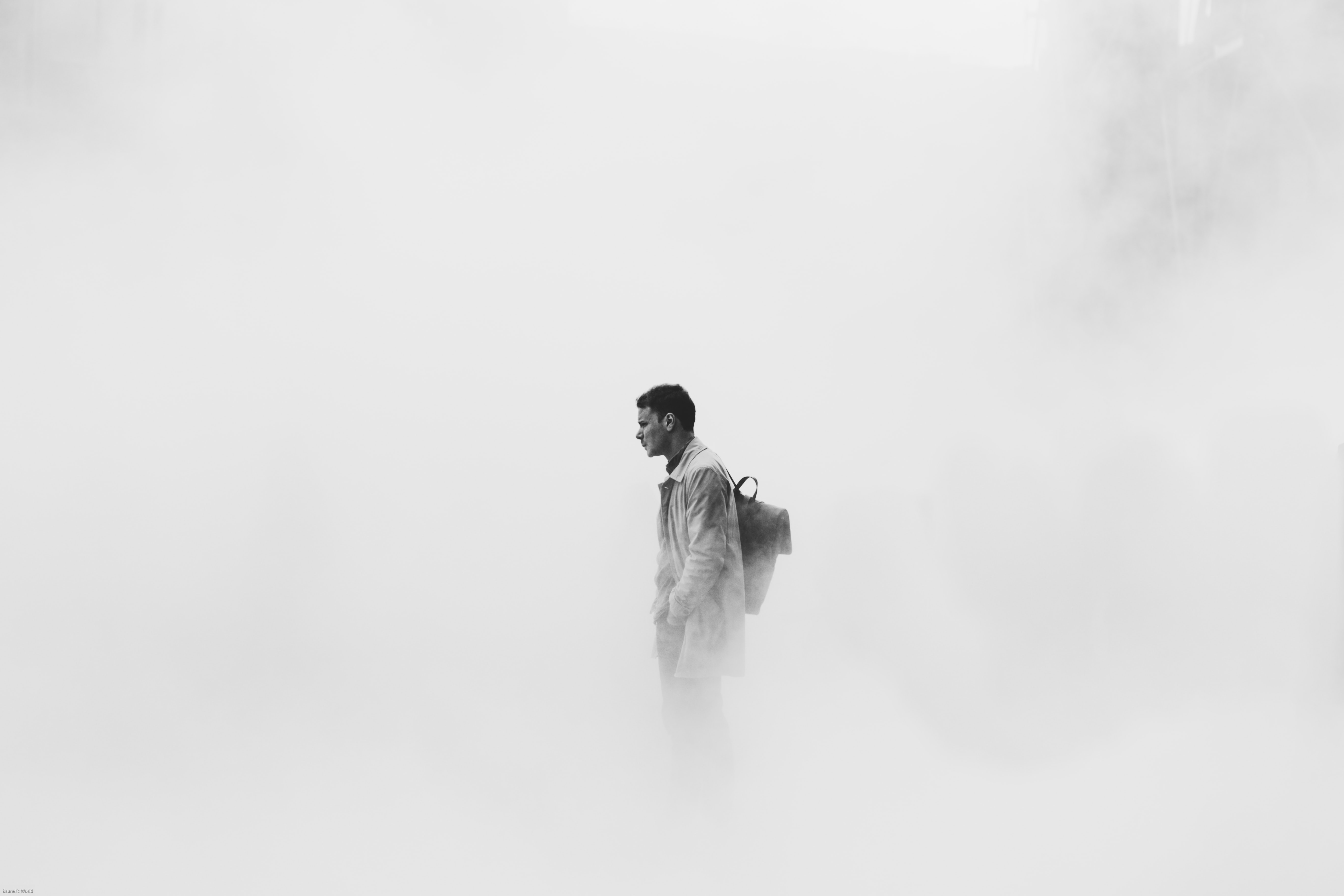 grayscale photo of man surrounded by fogs