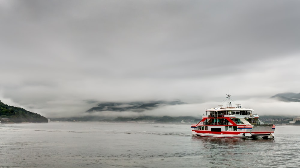 white and red barge on body of water