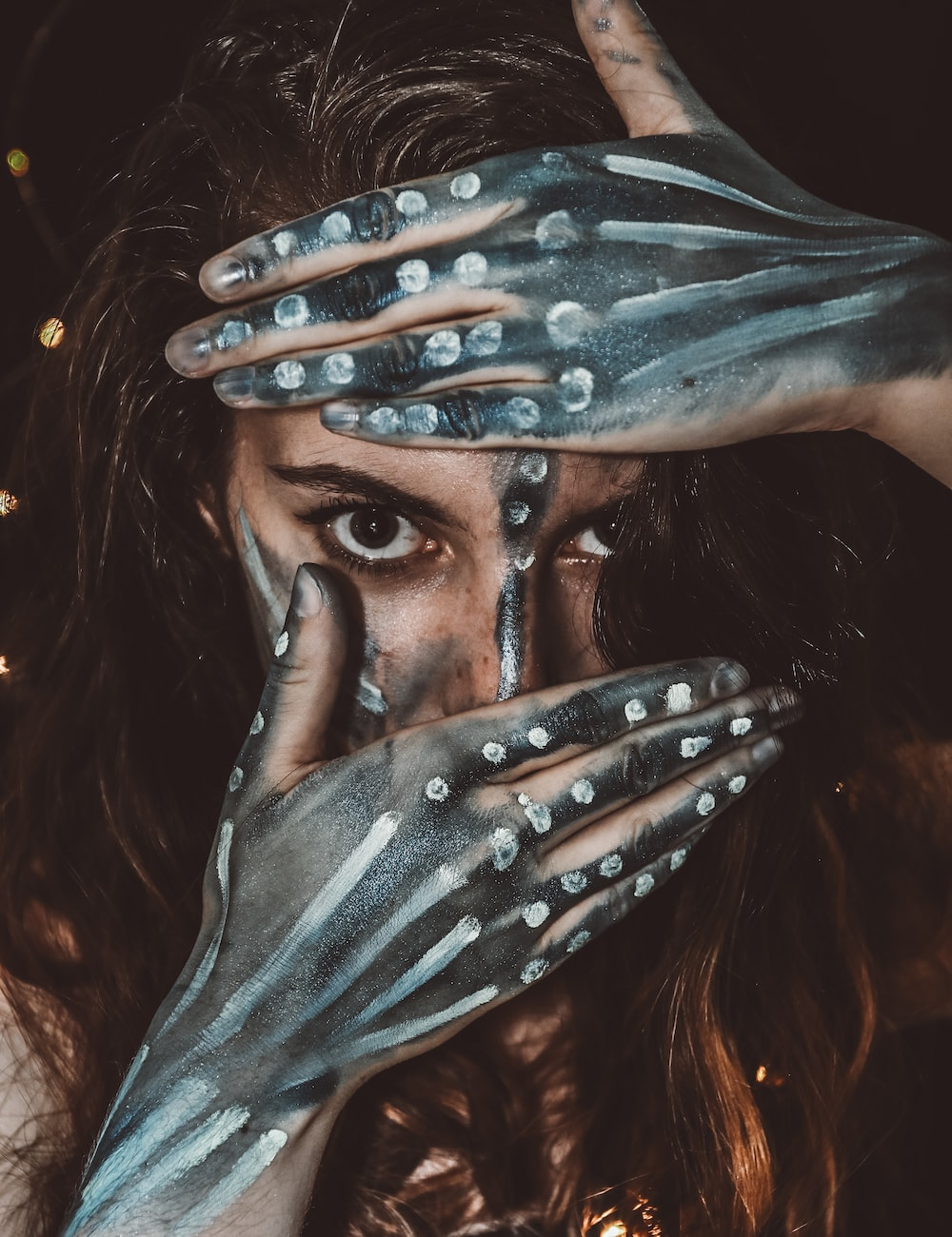 woman with black and white body paint covering half of her face with her hands