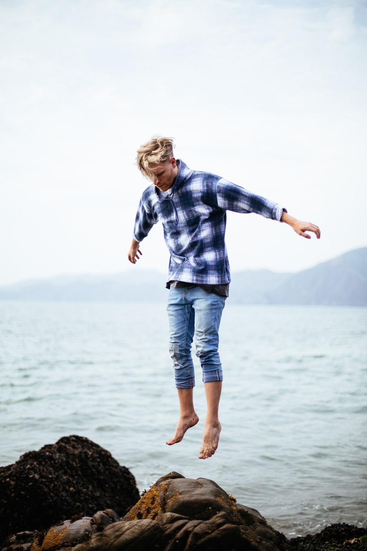 man jumping on rock near body of water