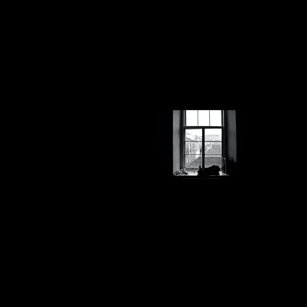 closed glass-panel window inside dark room