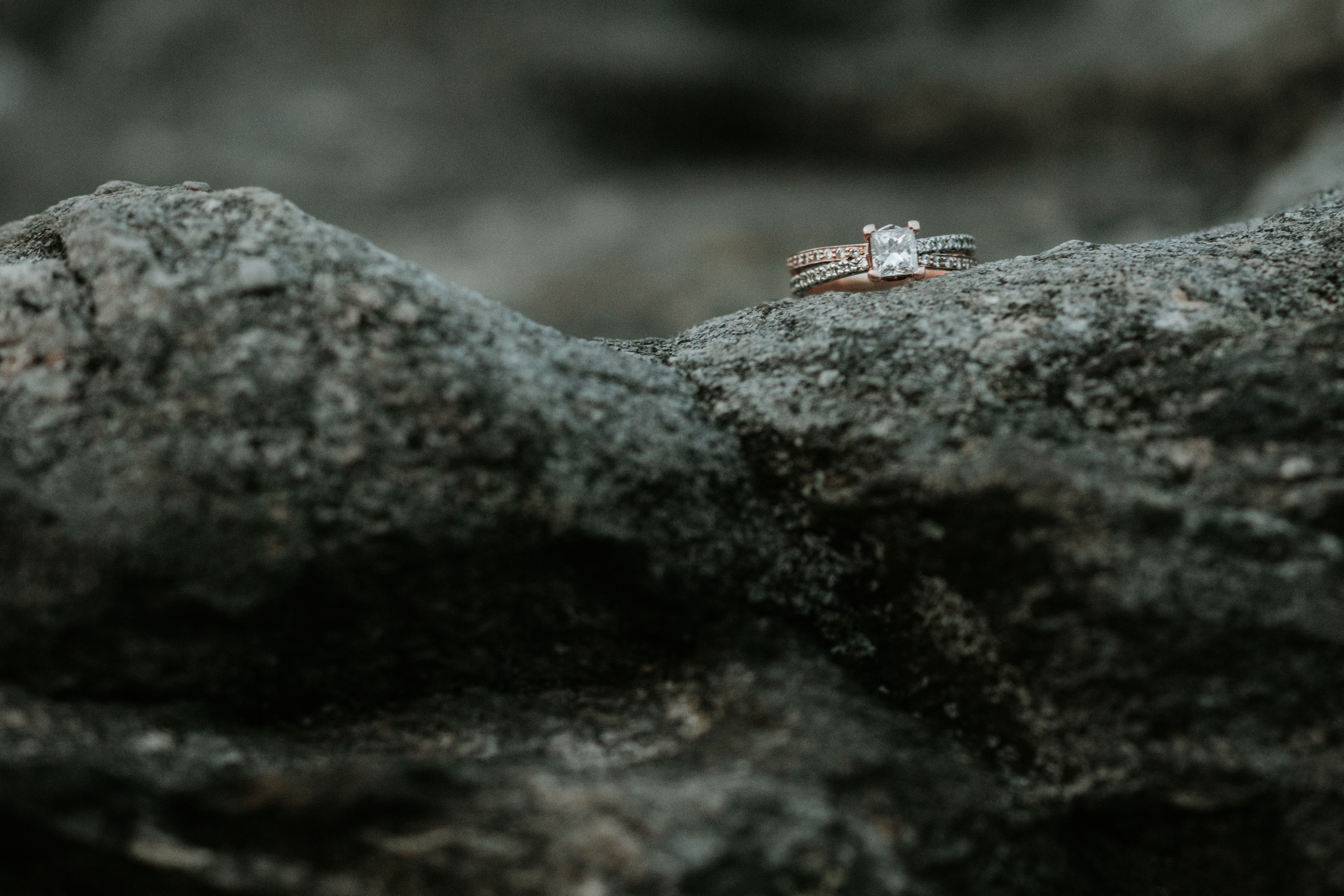 gold-colored clear gemstone encrusted ring on rock