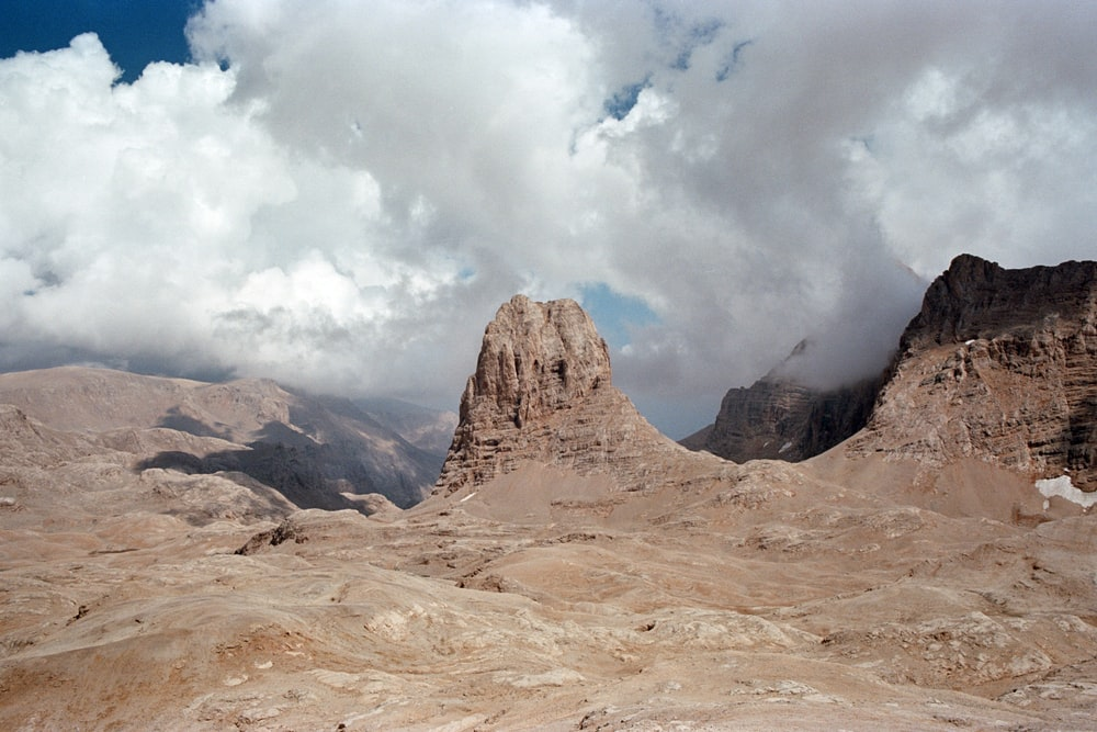 brown rock formation under white clouds at daytime