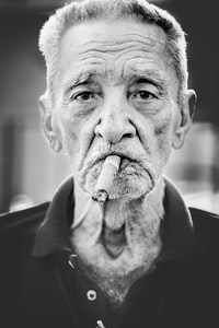 grayscale photography of man smoking cigar