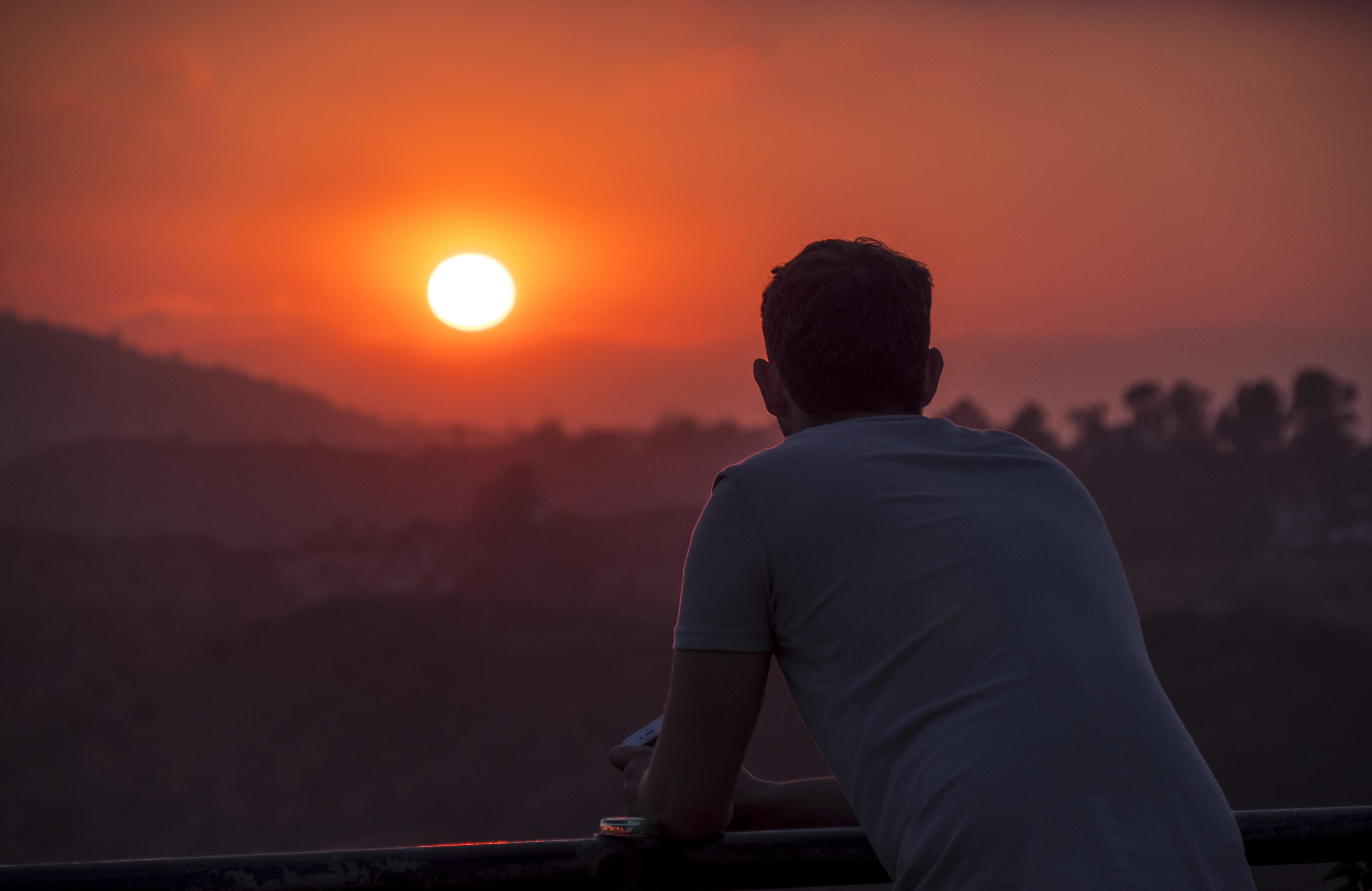 man wearing blue shirt looking at sunset