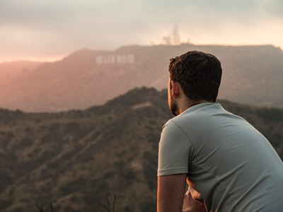 man standing in front of Hollywood signage
