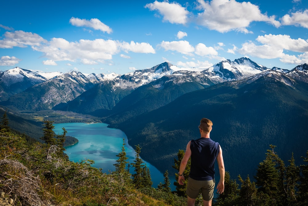 man standing facing body of water and mountains during daytime