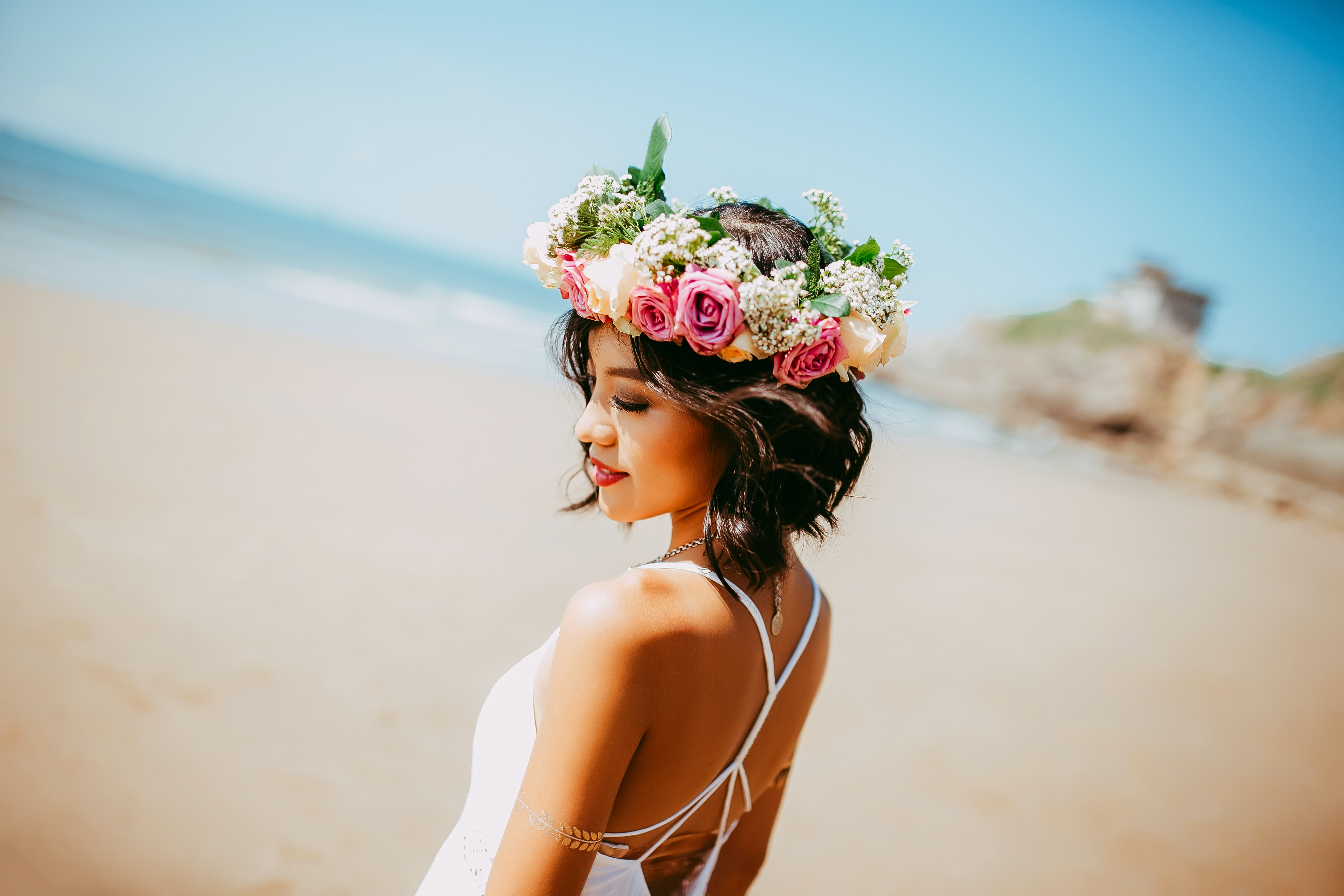 woman wearing white halter dress and floral tiara at shore during daytime
