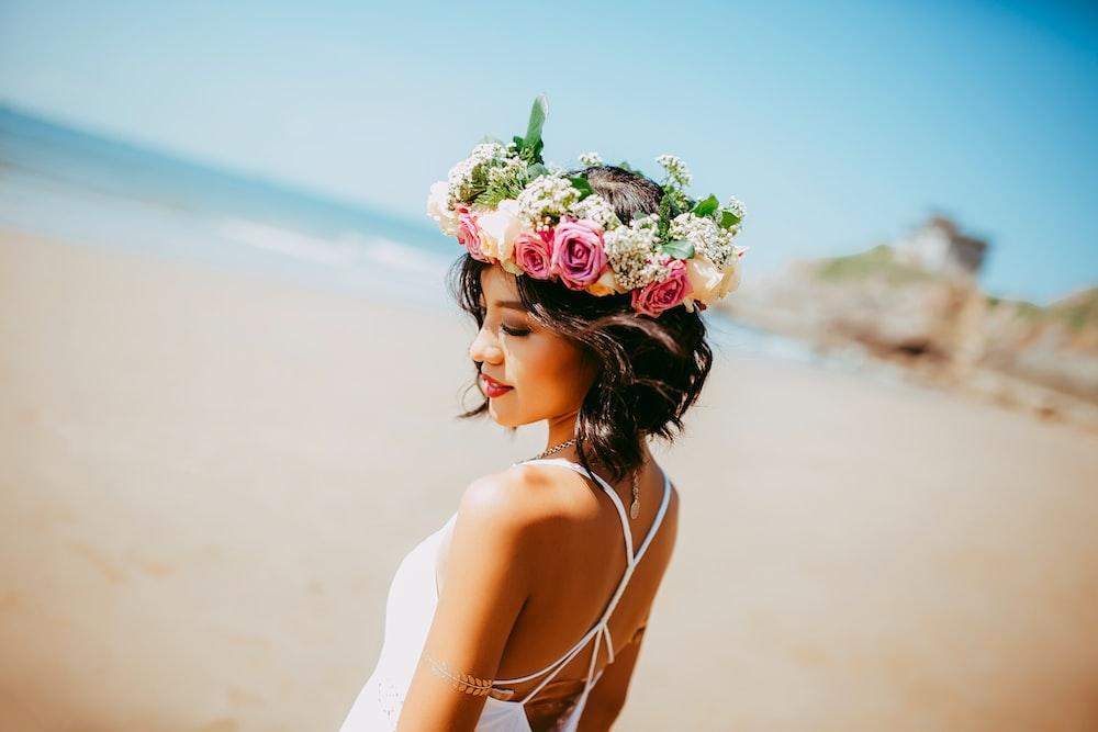woman wearing white halter dress and floral tiara at shore during daytime