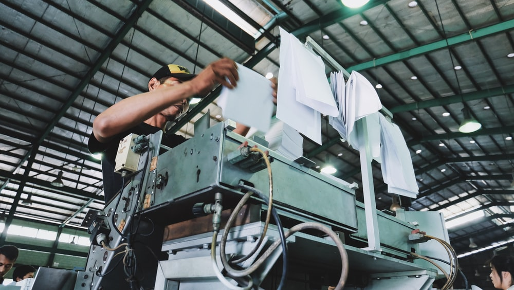 man holding bunch of white papers while operating large gray industrial machine inside well lighted room