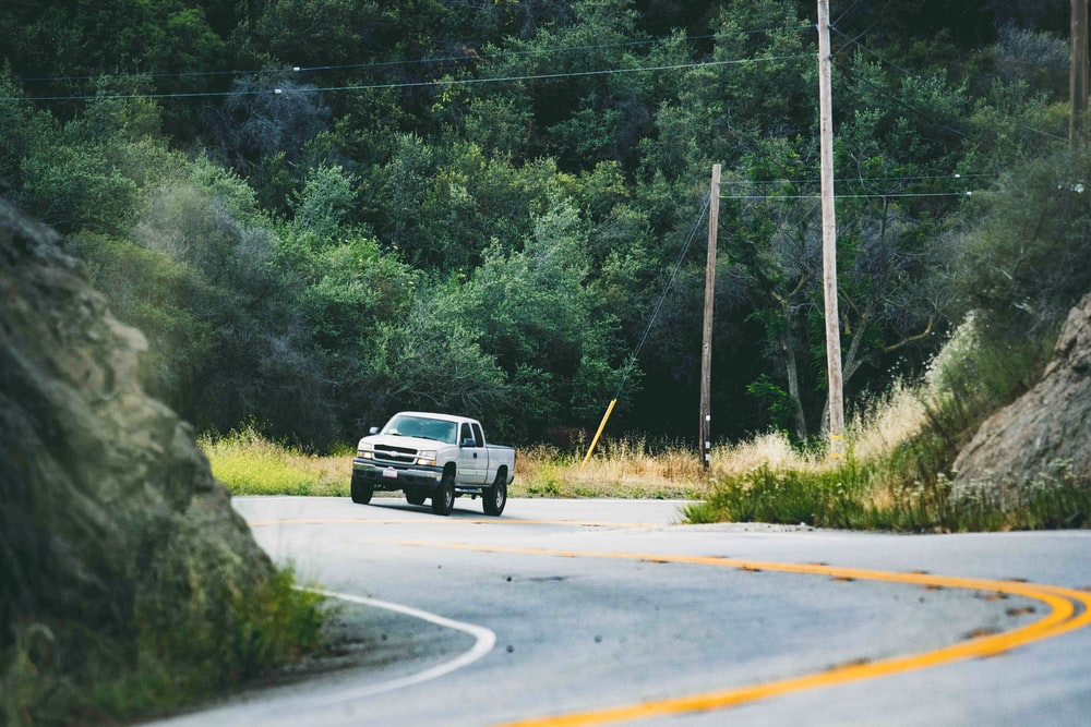 photo of incoming silver pickup truck on road beside hill during daytime