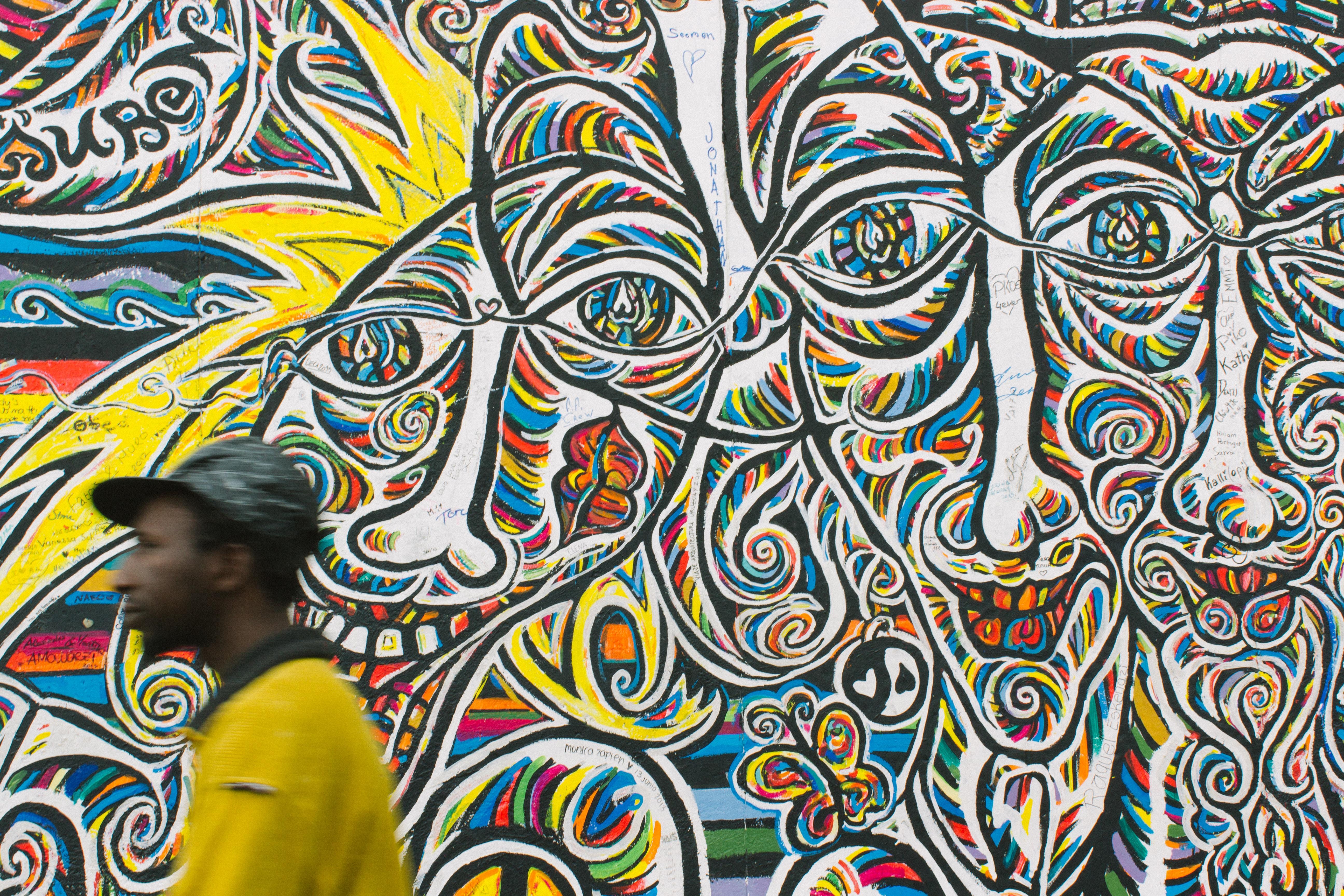 man standing near graffiti art