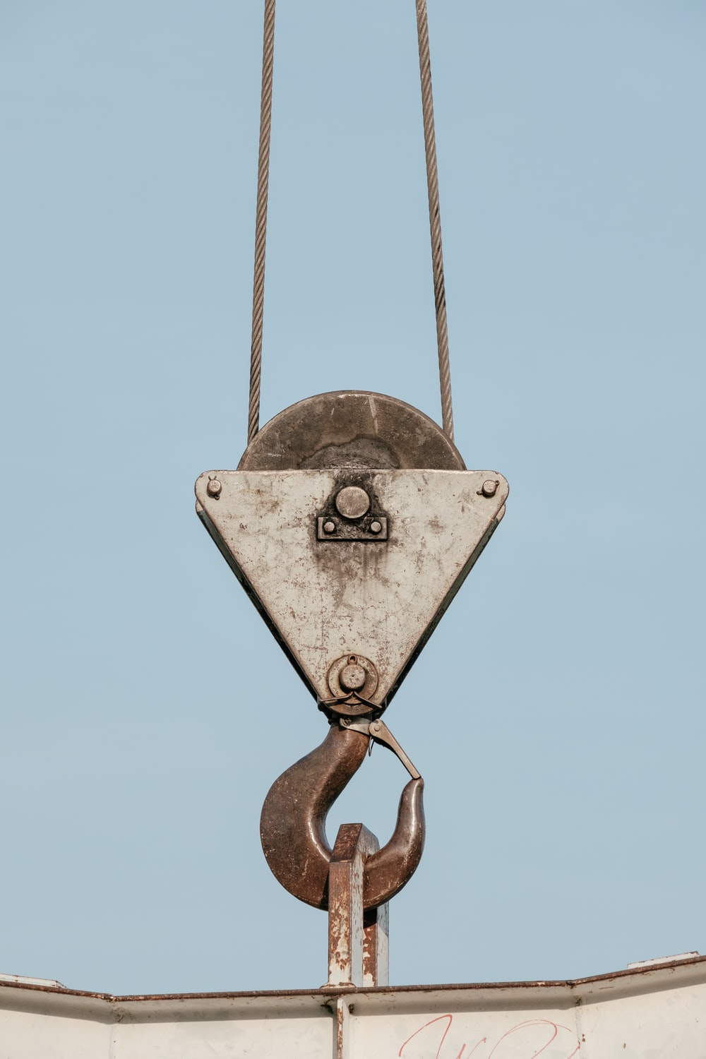 brown steel pulley holding white steel bar