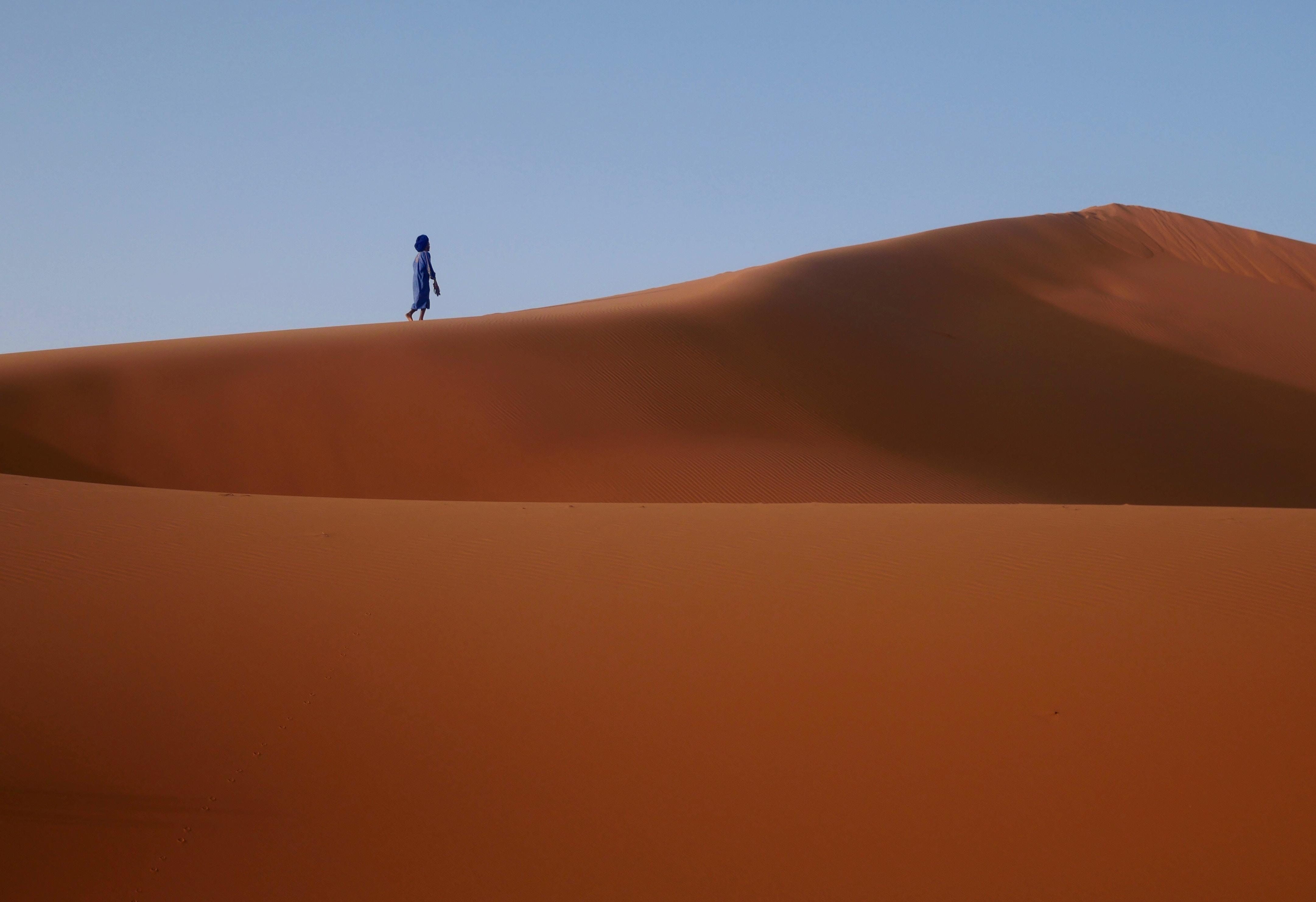 silhouette of person walking on desert