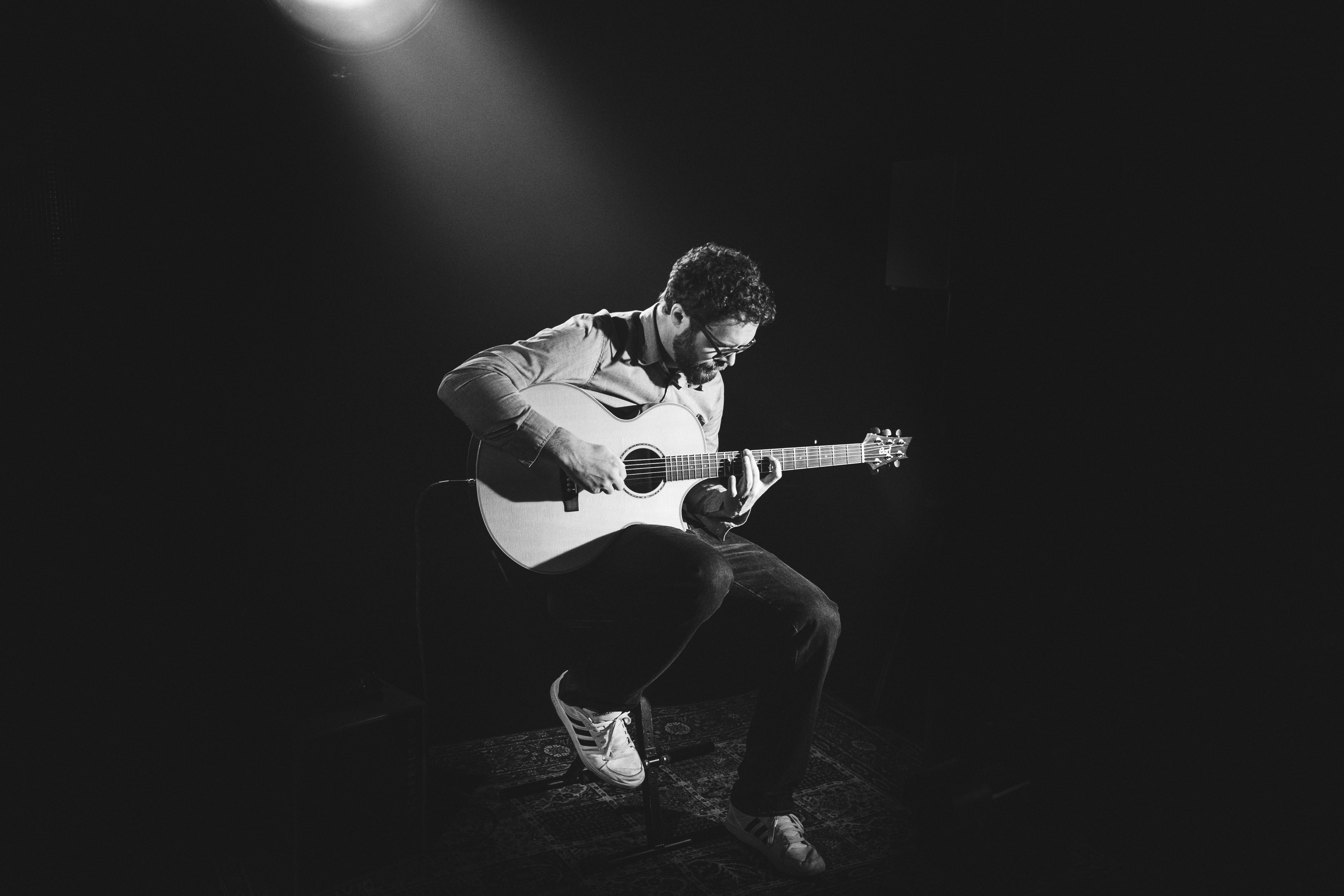 grayscale photo of man playing guitar on stage