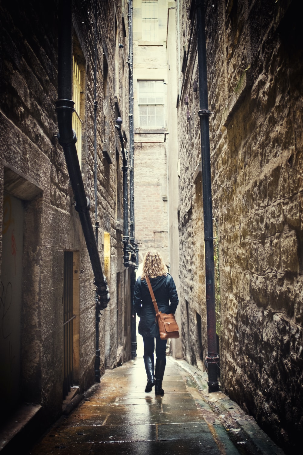 woman carrying brown leather shoulder bag walking on narrow concrete pathway between concrete buildings during daytime