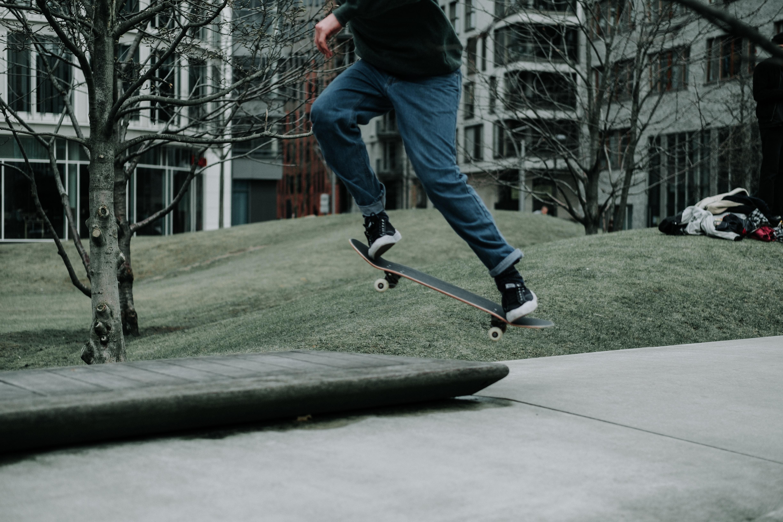 person doing ollie flip kick on skateboard