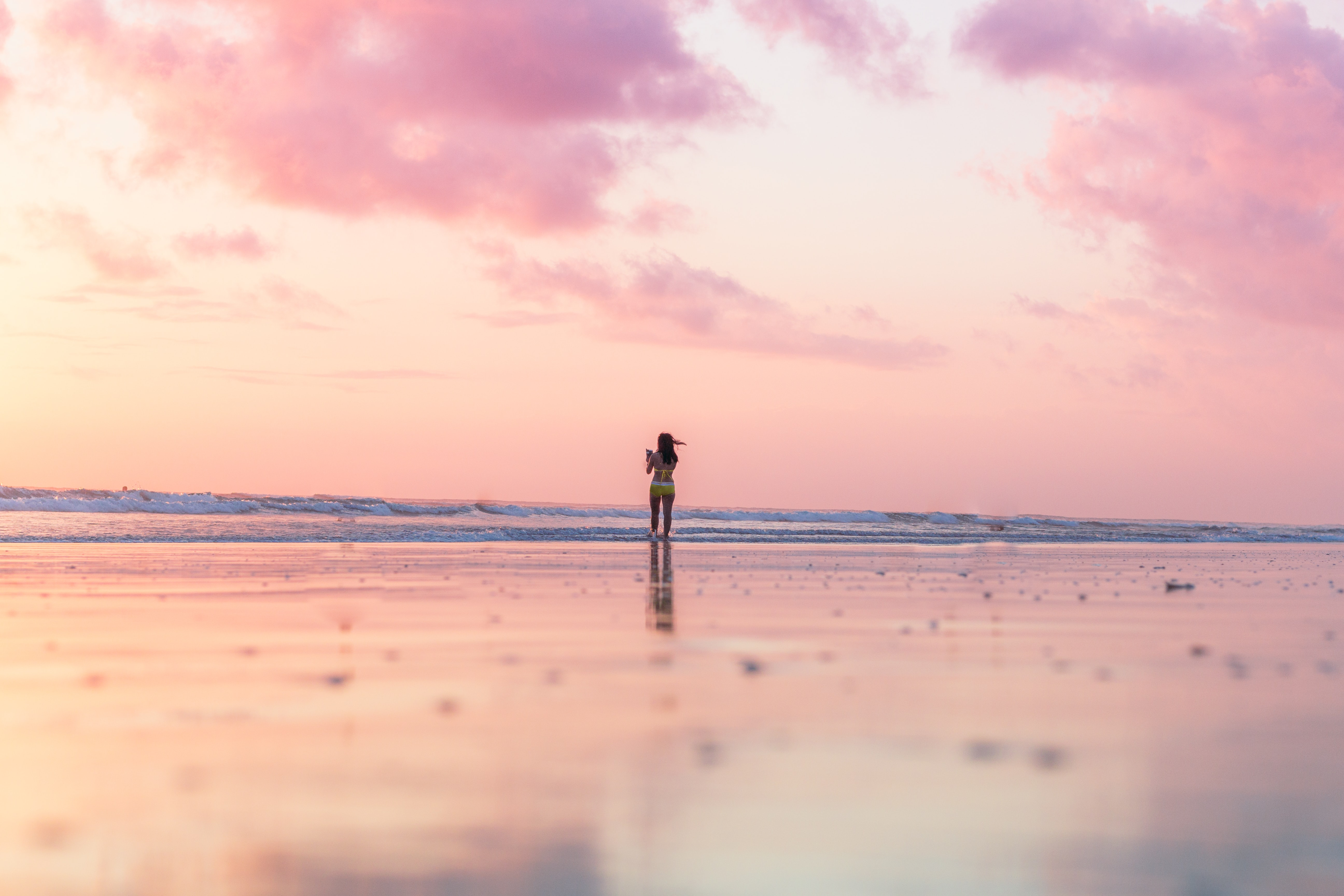 woman standing on seashore in front of body of water