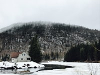 white house near river surrounded by snow-covered land