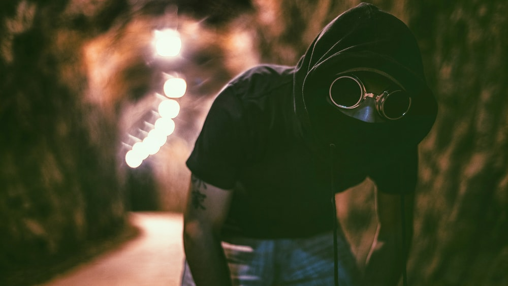 man with kanji text bicep tattoos wearing black hoodie and blue denim bottoms