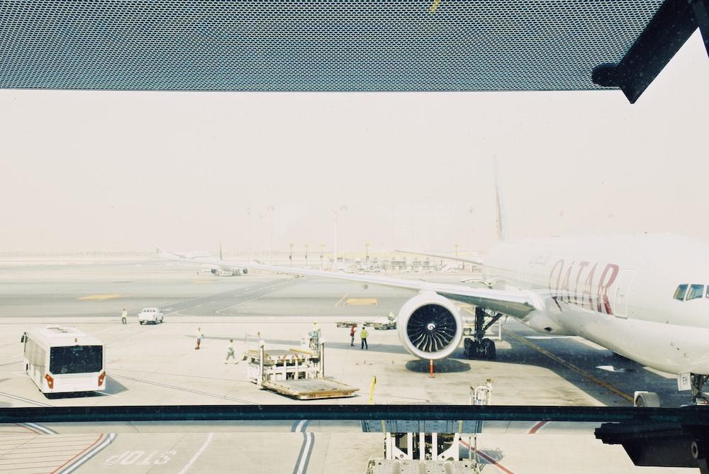 white Qatar airplane on airport during daytime