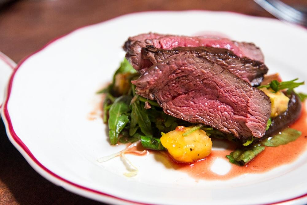 medium rare sliced steak in white ceramic plate