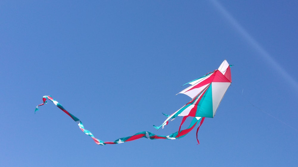 photo of white, blue, and red kite under blue sky
