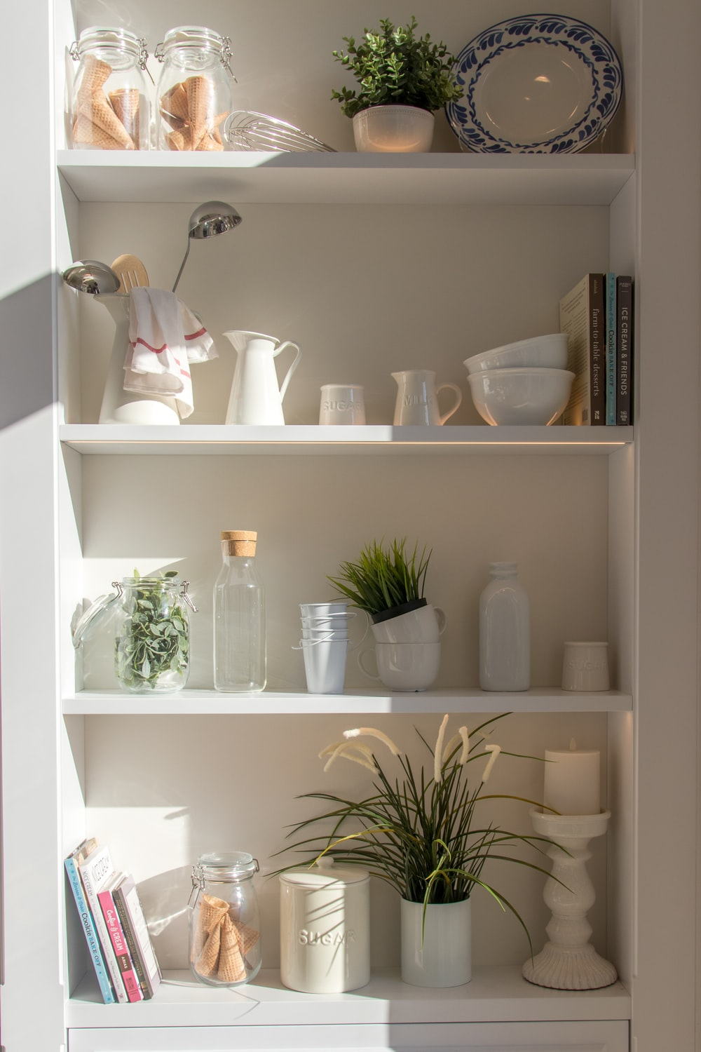 bowls and bottles in white wooden 4-layer shelf