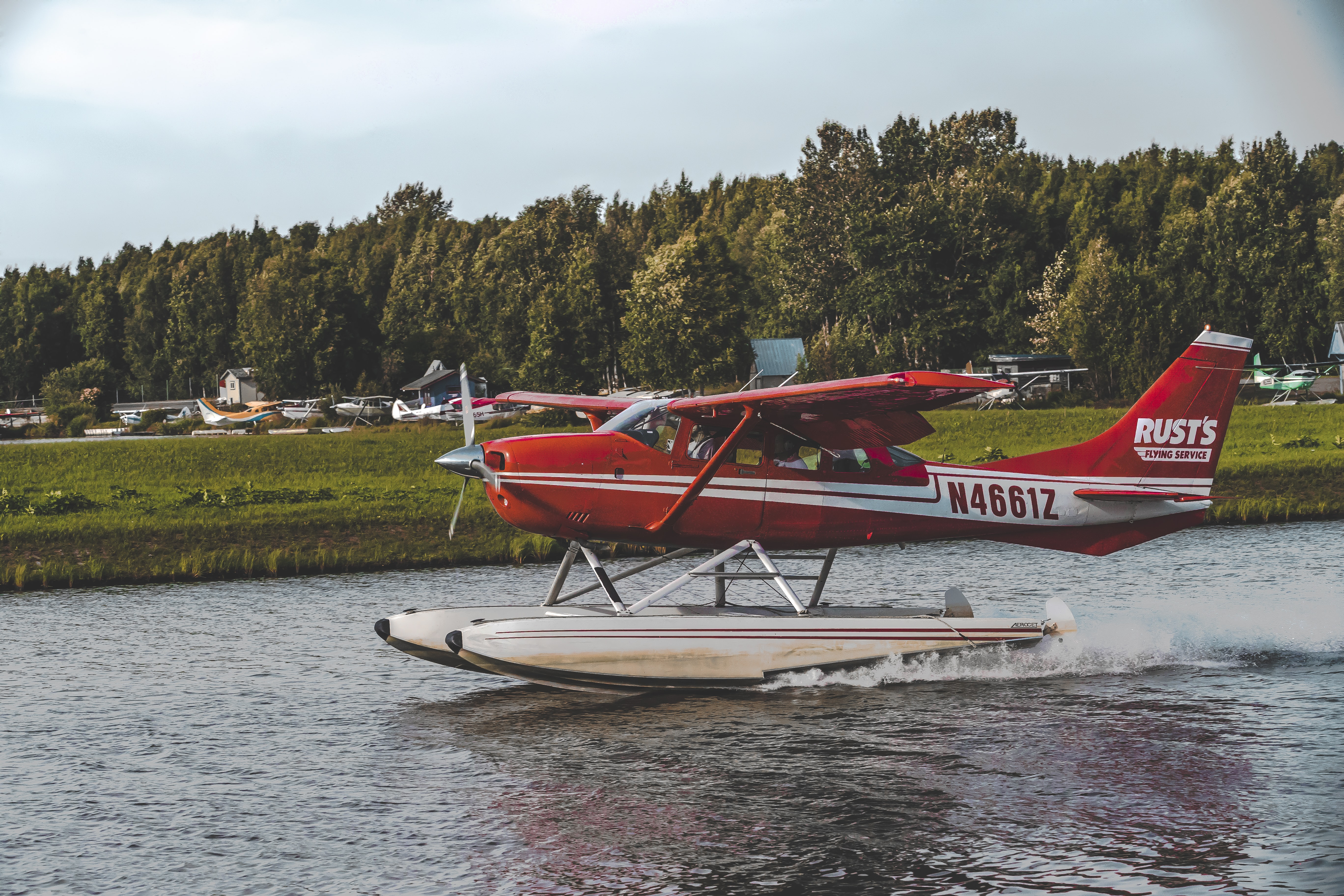 red and white Rusts N46612 biplane on body of water