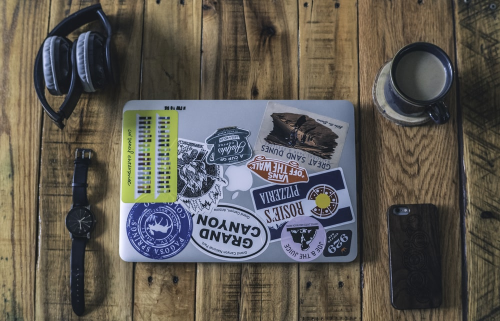 laptop near watch, headphones, phone and cup of coffee on brown wooden table