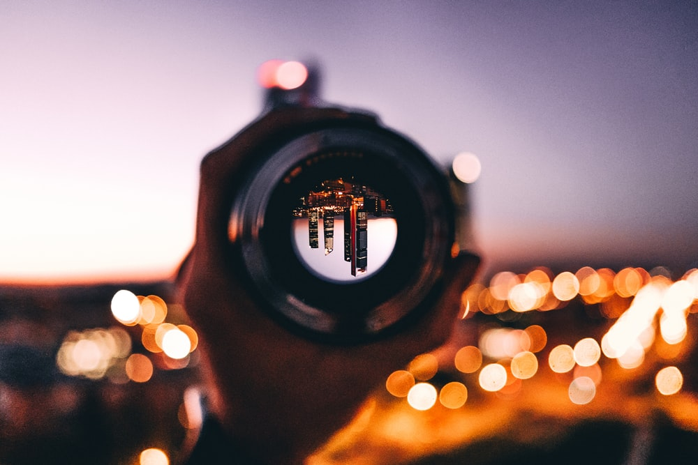 shallow focus photography of person holding camera lens
