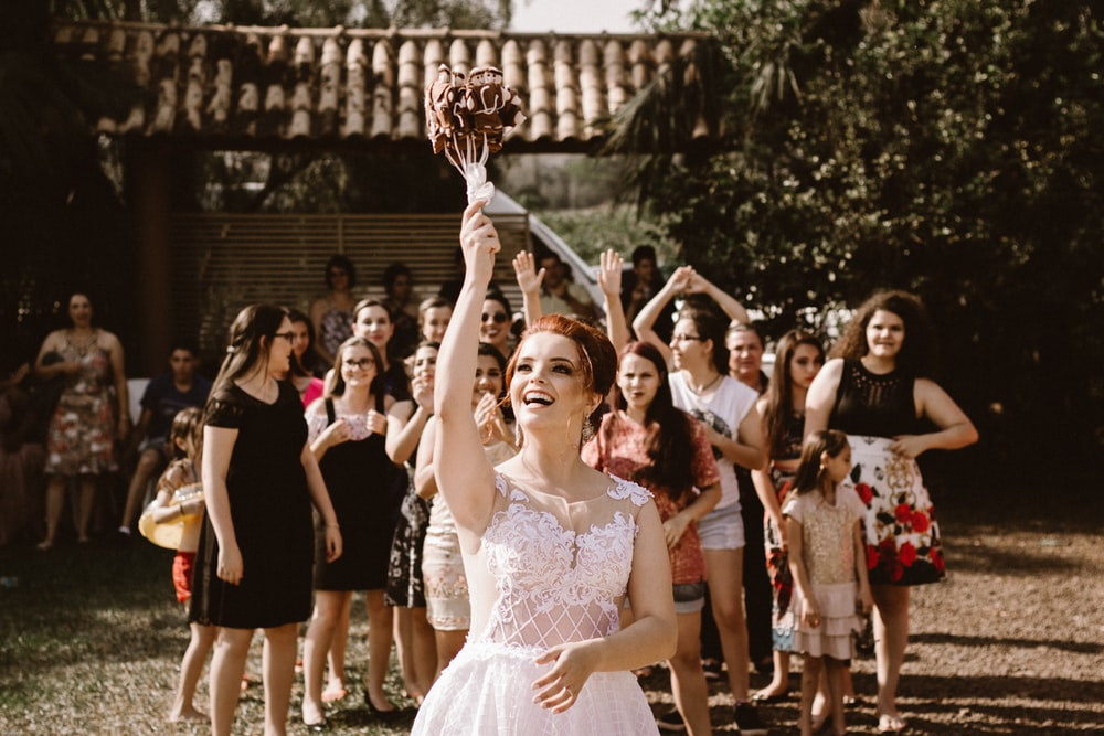 bride throwing flower bouquet on women during daytime