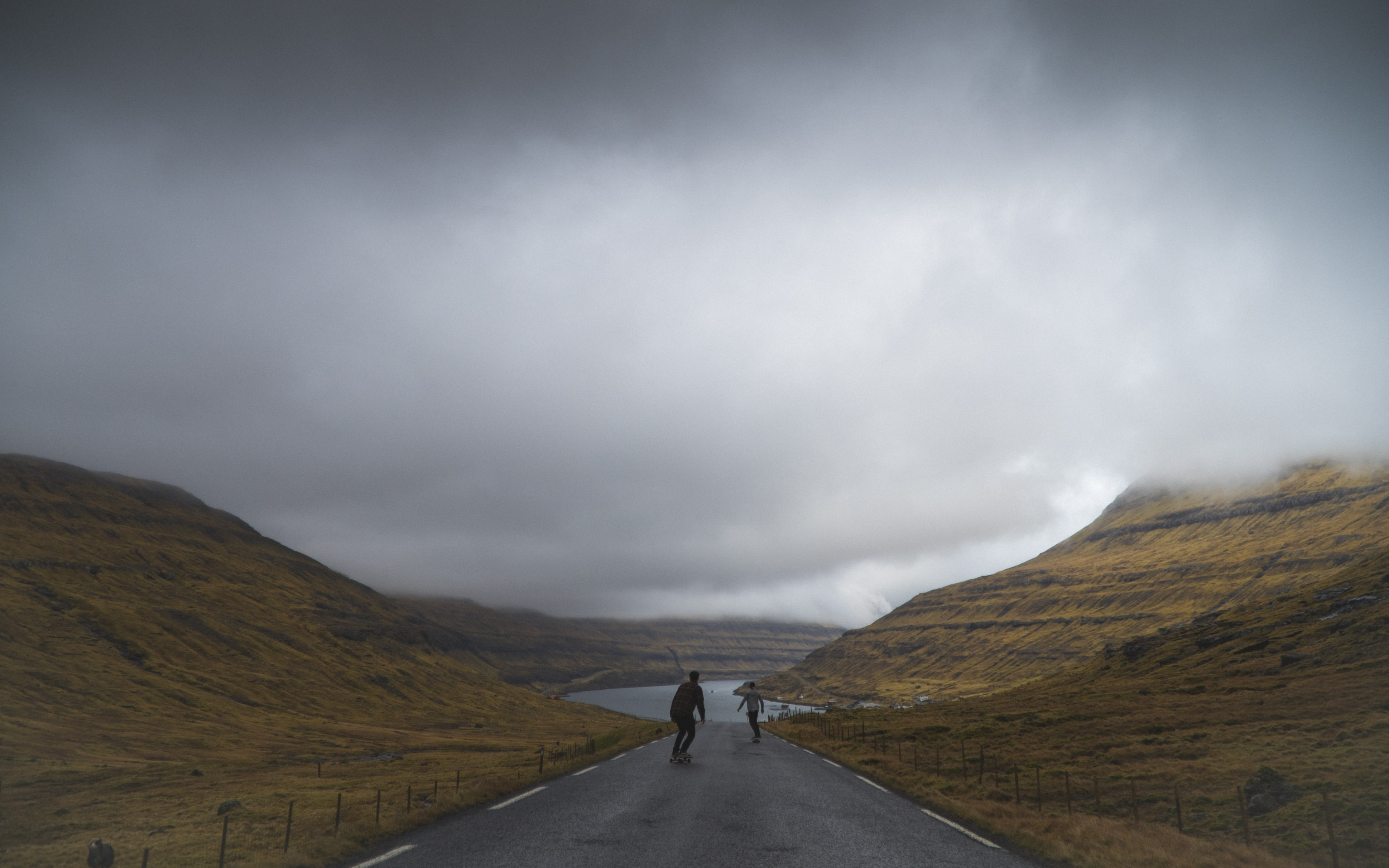 person in black jacket standing on road under cloudy sky
