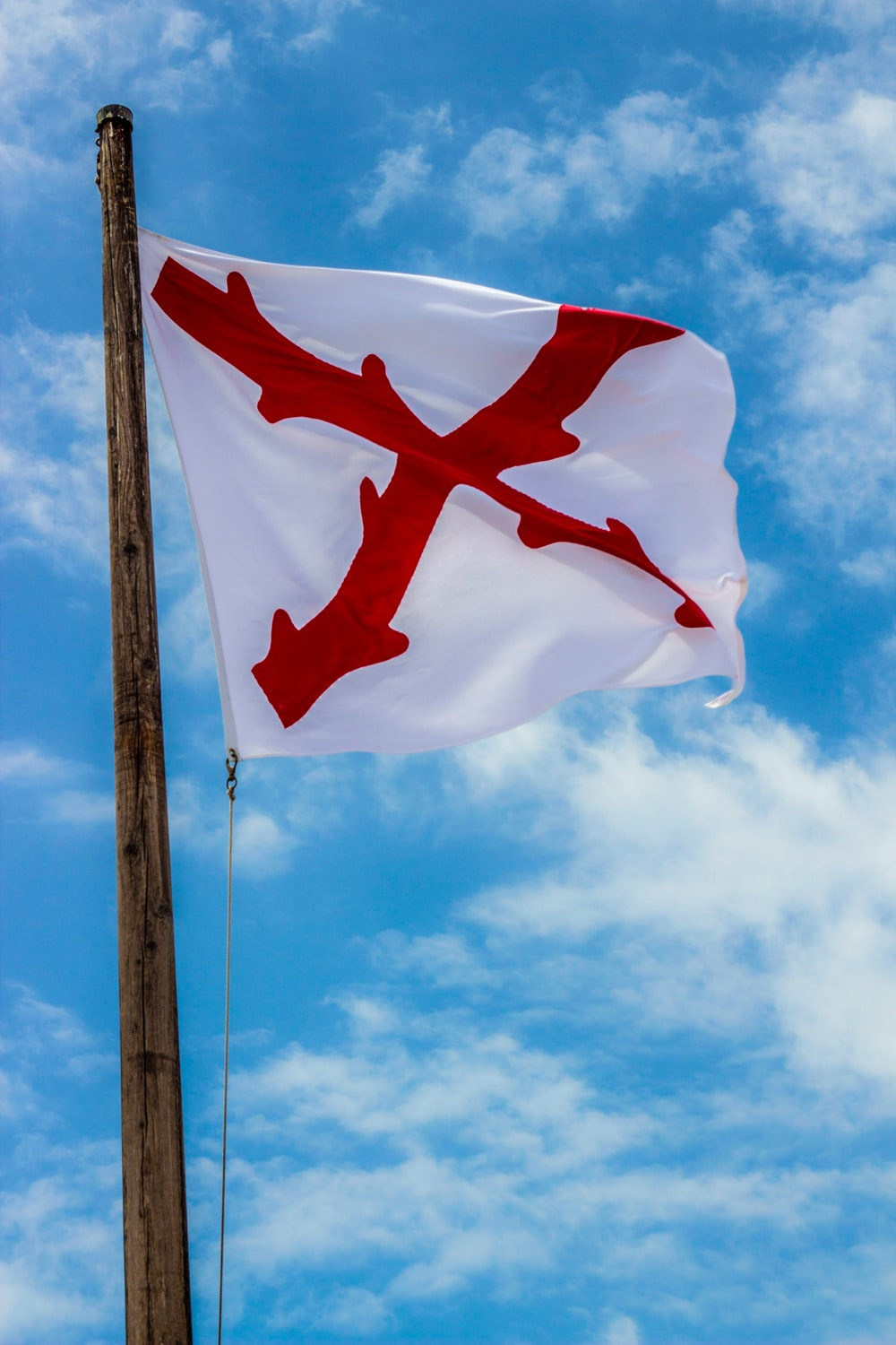 white and red cross flag under blue sky