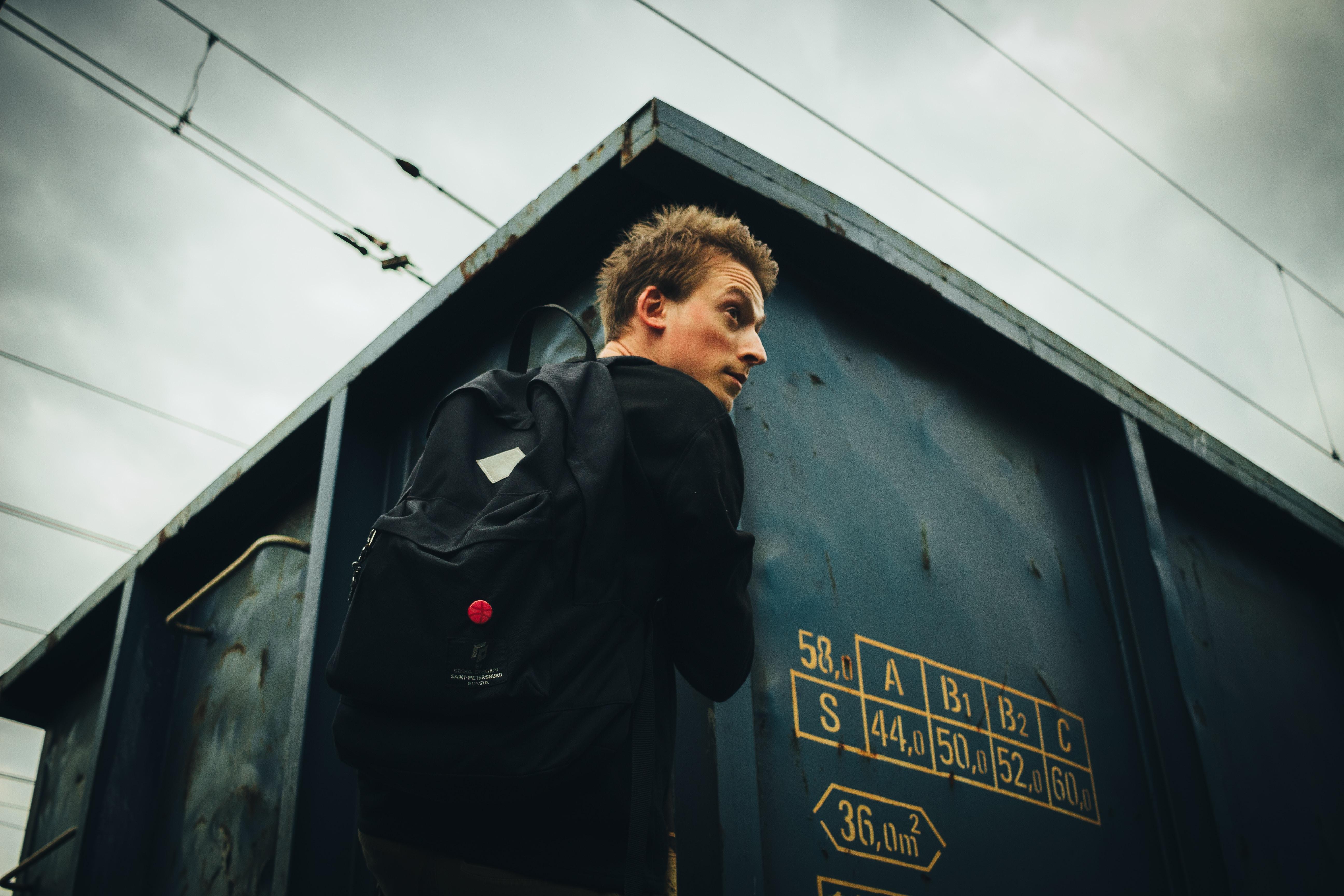 man wearing black backpack beside building