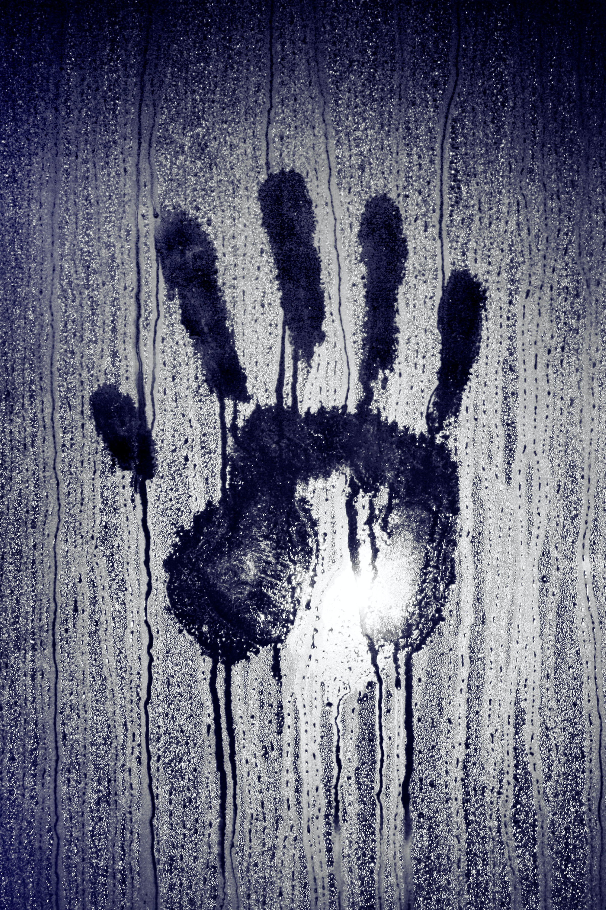 person's hand print on moistened glass