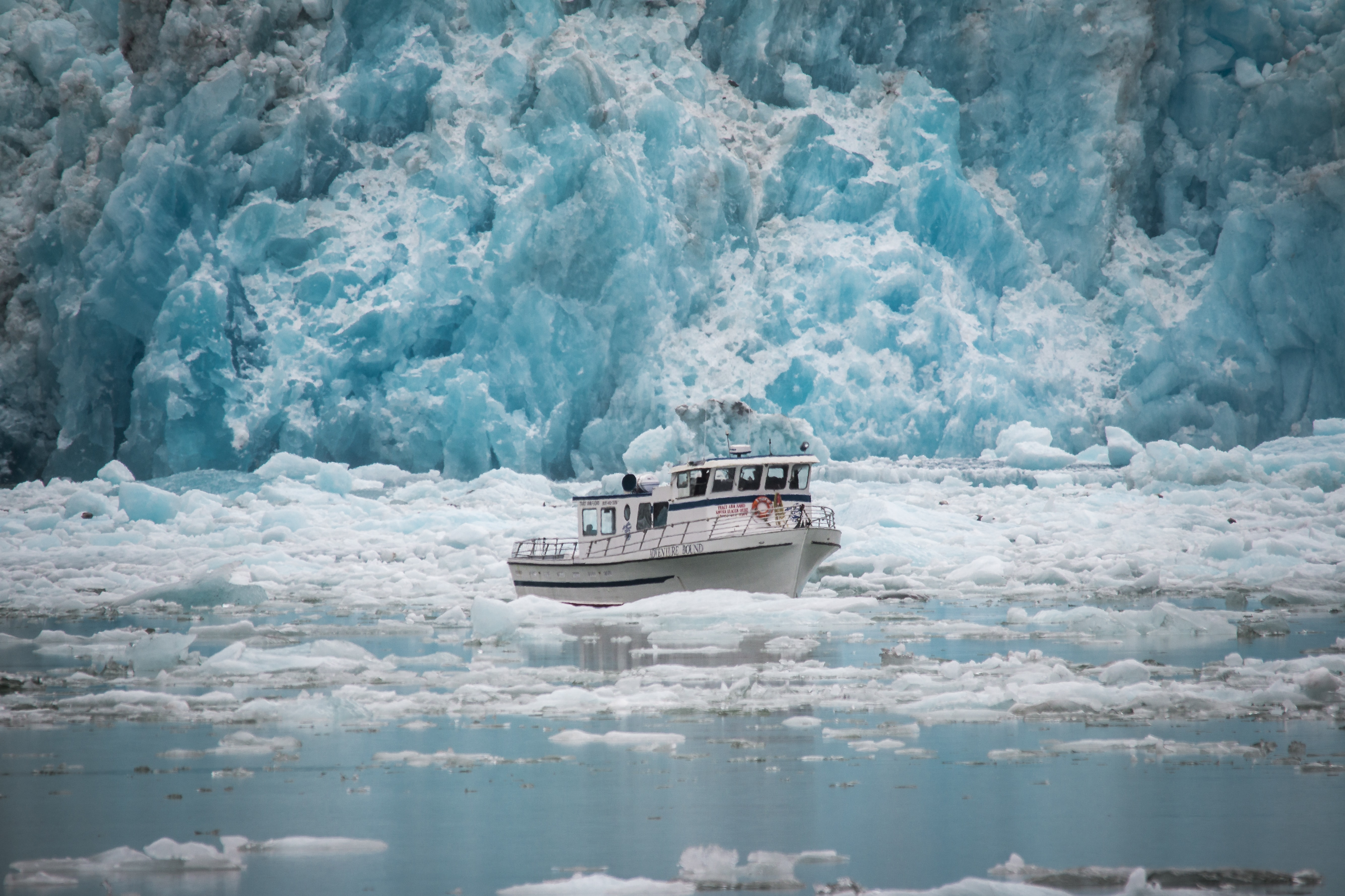 white boat surrounded by floating ice