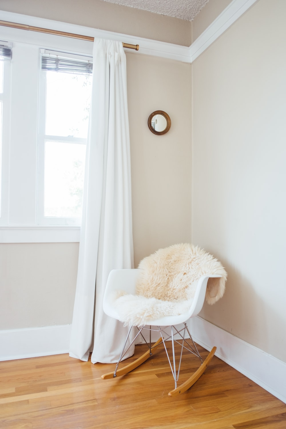white and brown rocking chair near white painted wall and white window curtain