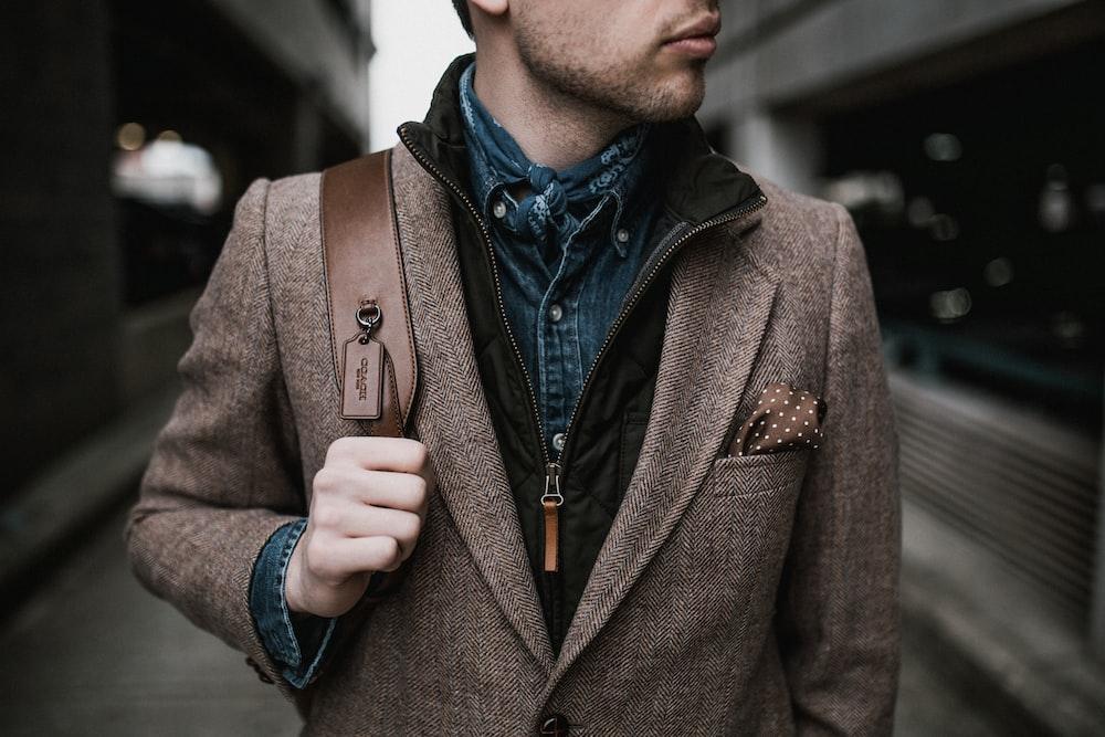 man in brown suit jacket carrying brown backpack