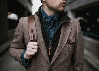 man in brown suit jacket carrying brown backpack