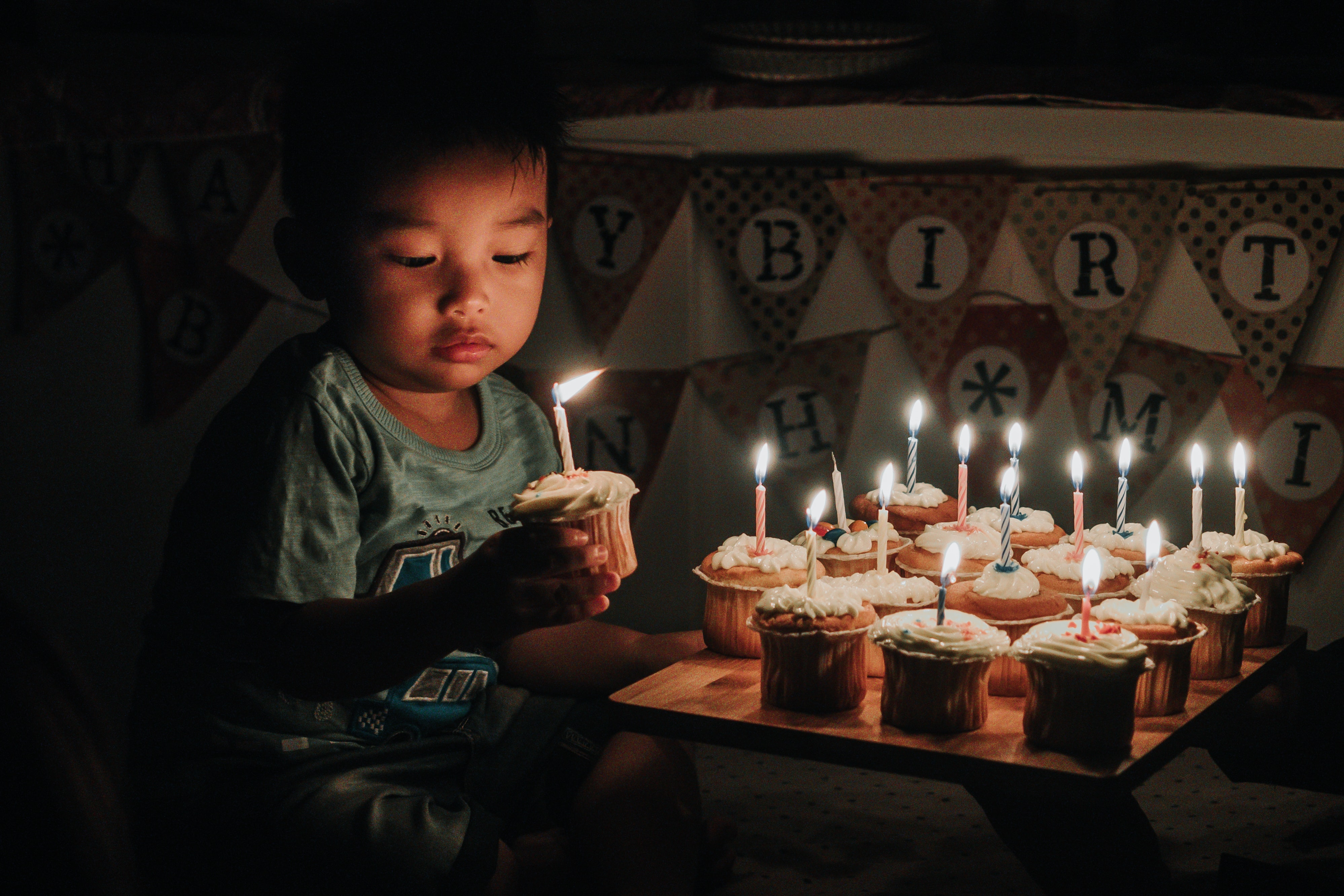 boy holding one of many cupcakes with lit candles