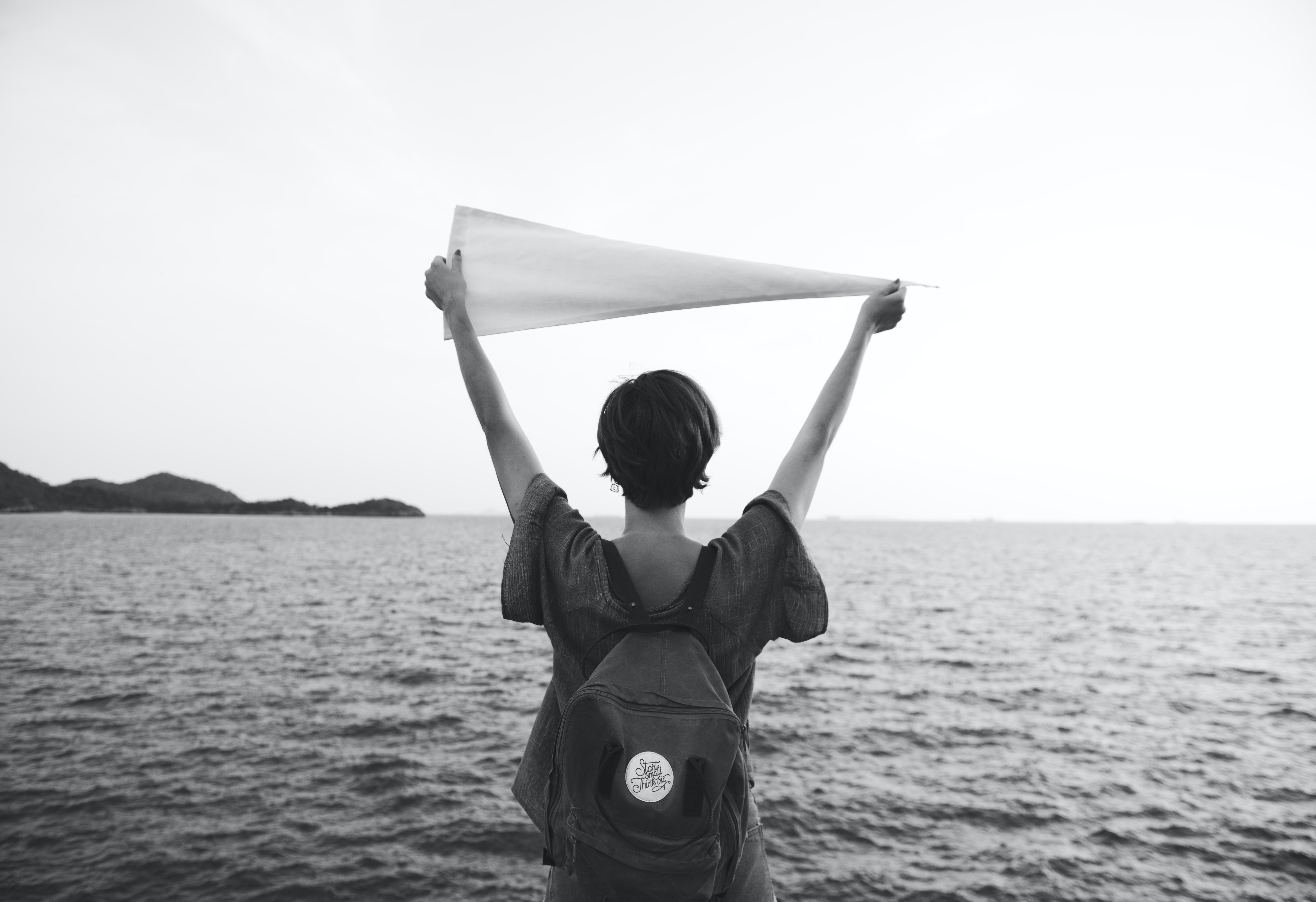 person raising hands while holding flag facing body of water