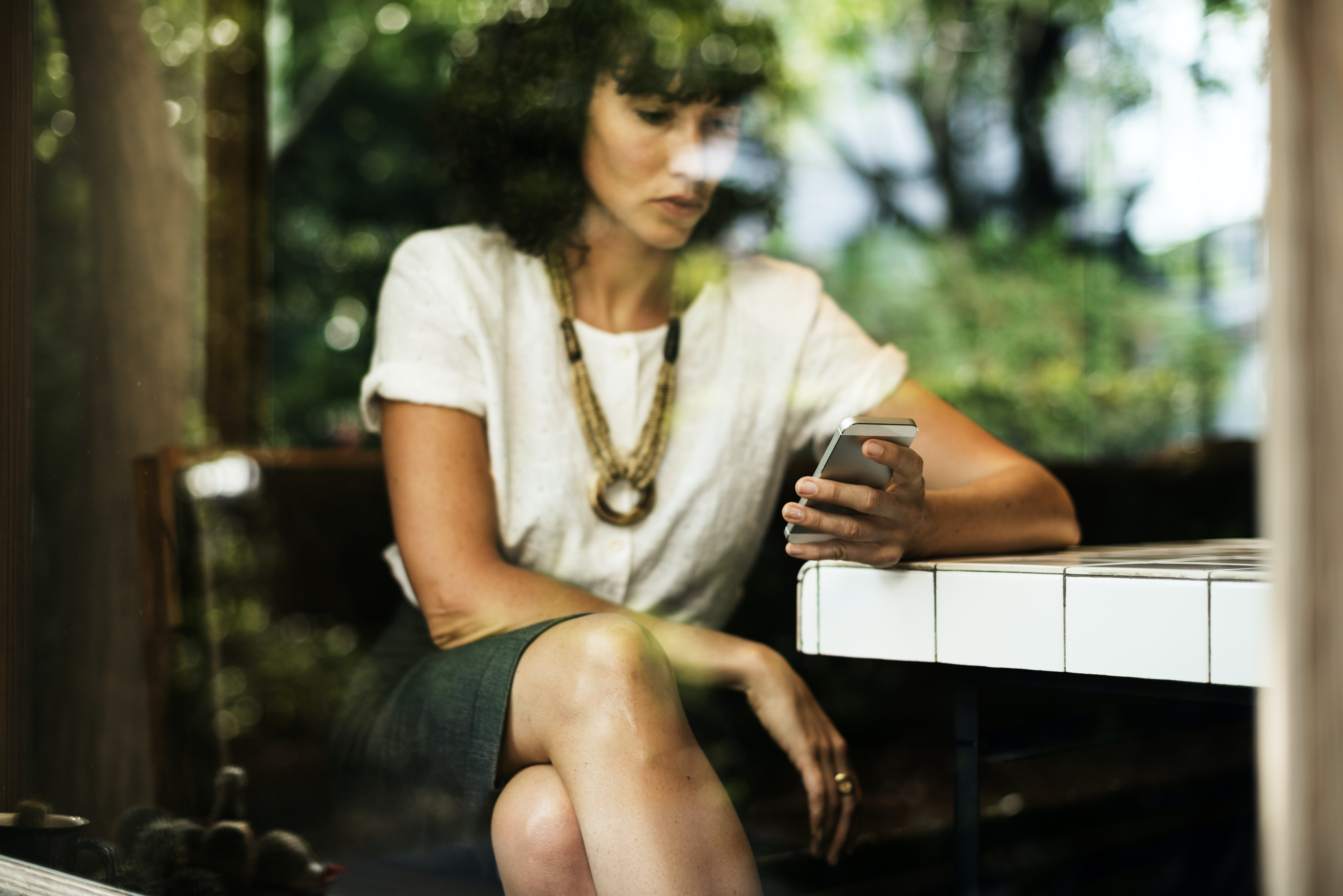 woman sitting while using her smartphone