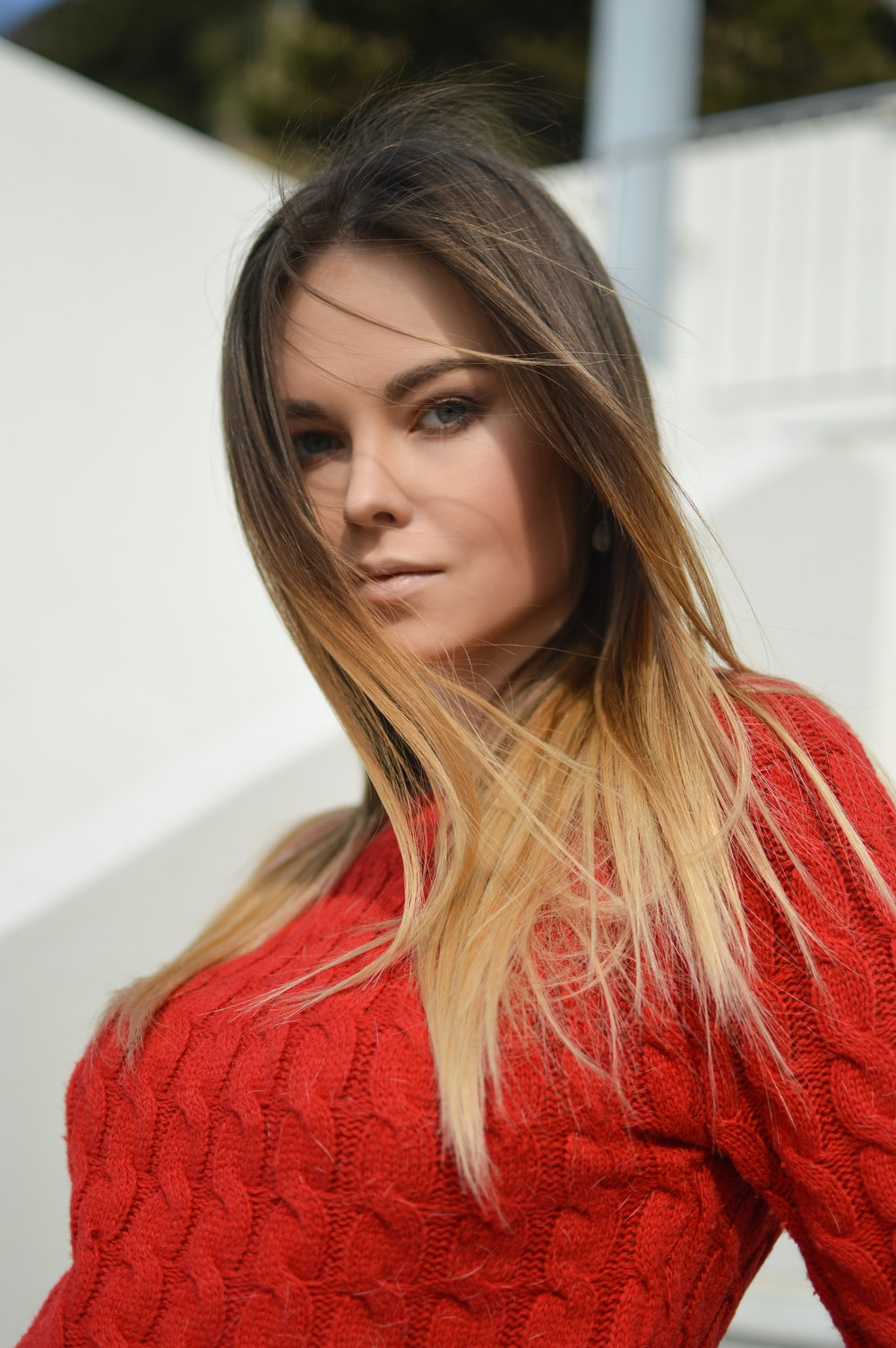 woman wearing red knit shirt with her hair being flown by the wind selective focus photo