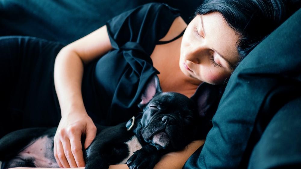 woman and black French bulldog sleeping on sofa