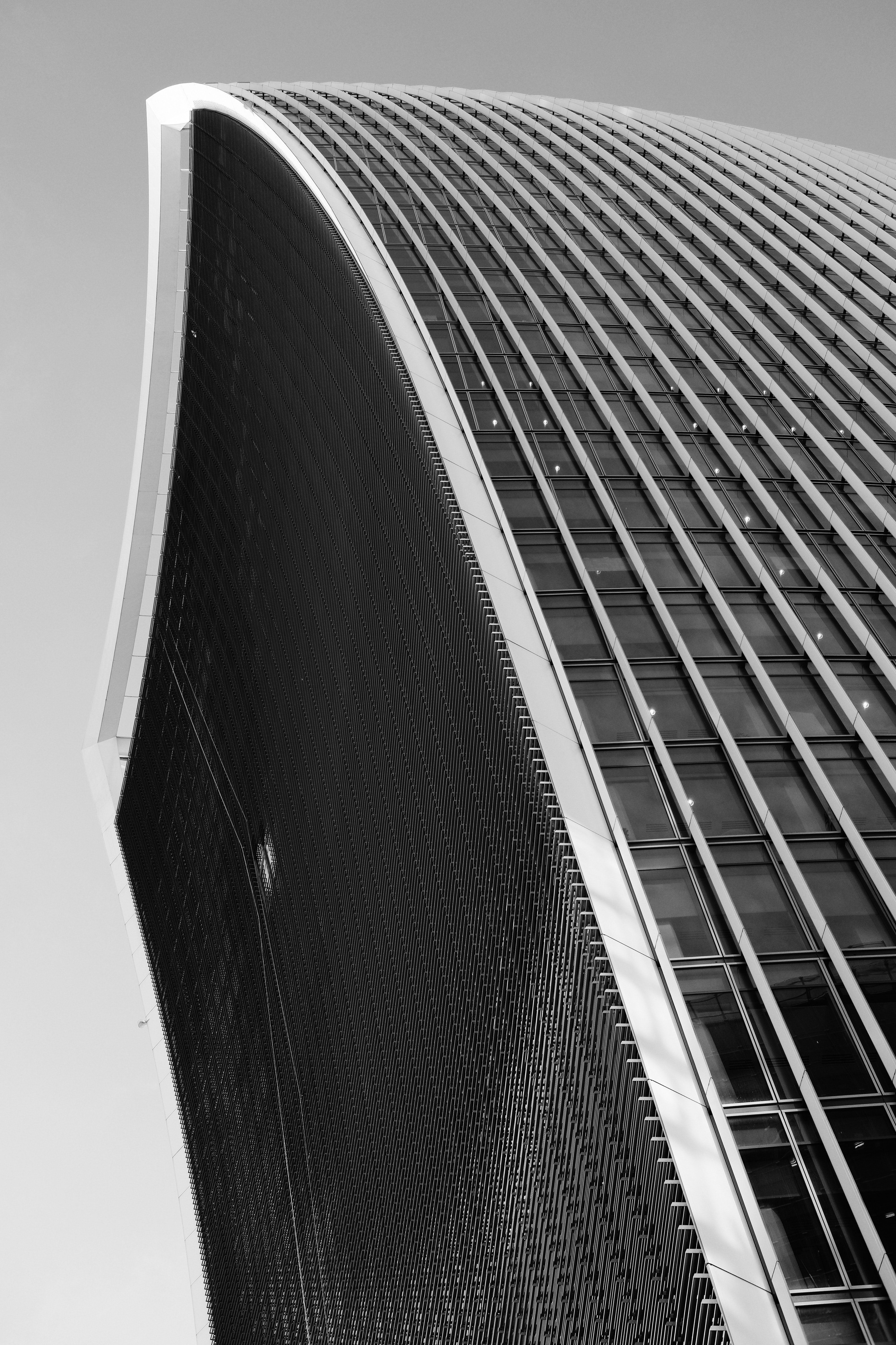 low-angle grayscale photo of curtain-wall building