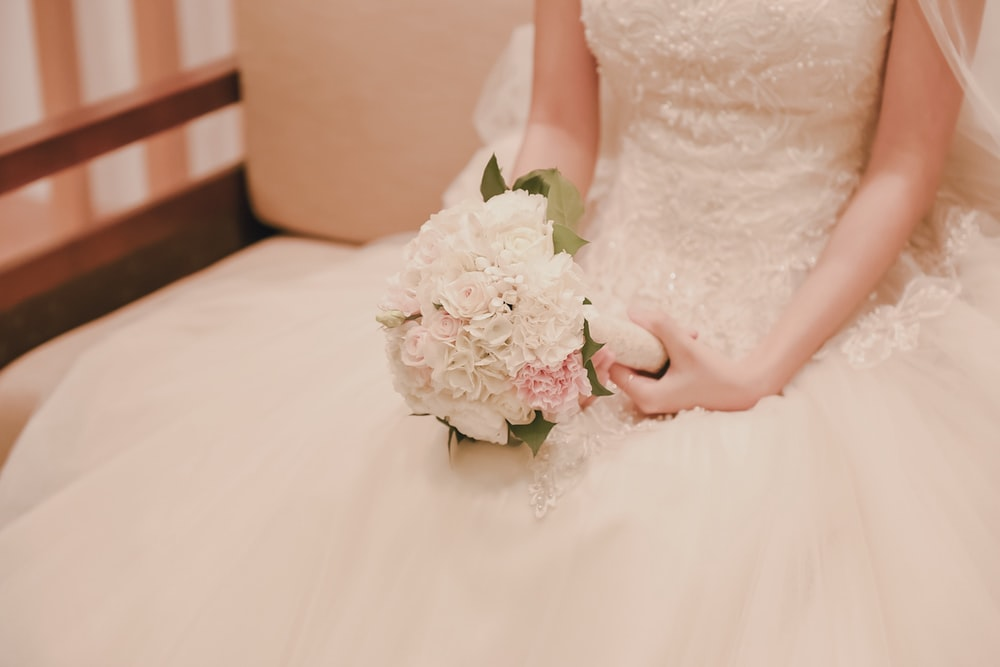 woman wearing wedding gown holding bouquet of flowers