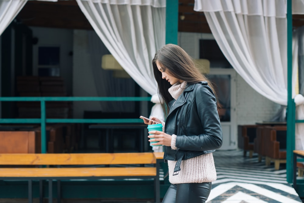 woman using phone while walking near green building