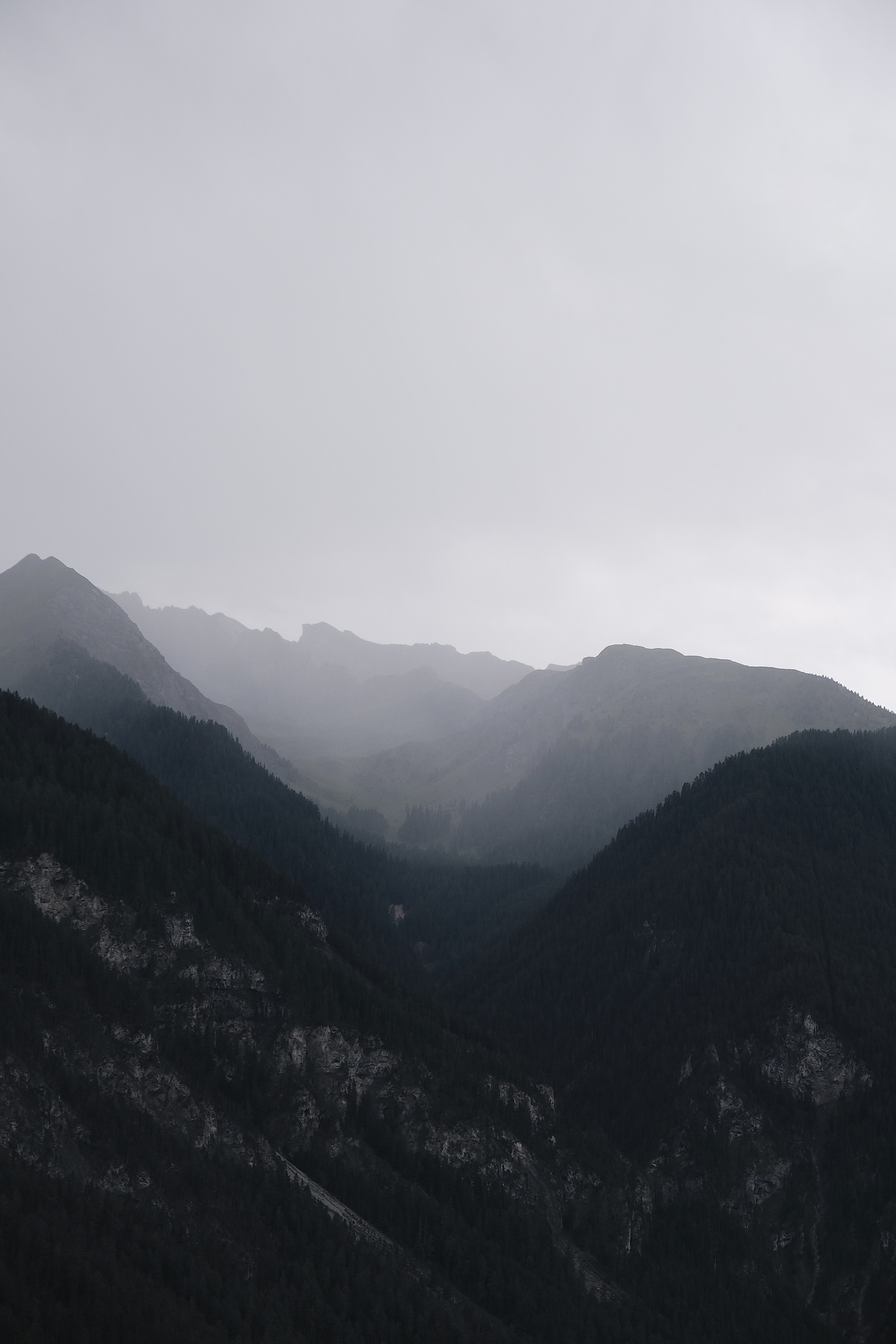 mountain range under cloudy sky during daytime
